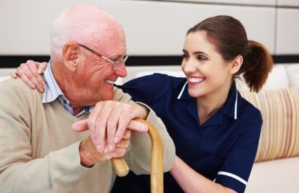 Young woman nursing assistant sitting with an elderly person leaning on a cane