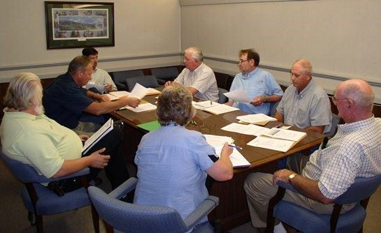 Soil and Water Conservation District board members gathered around a table during a board meeting